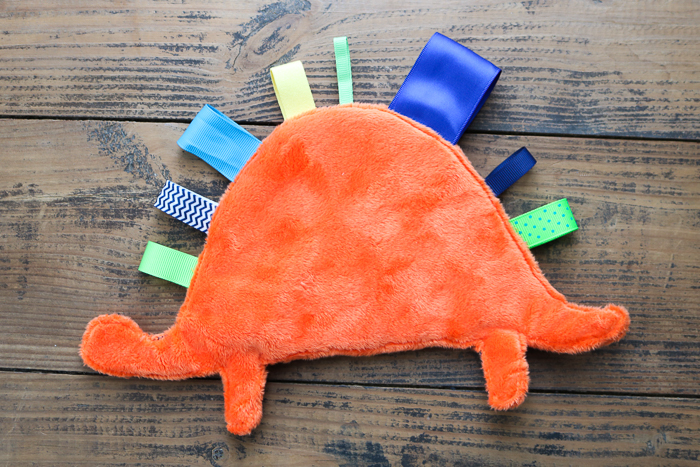 Make a baby tag blanket in a dinosaur shape with your Cricut machine in minutes! A fun project for a newborn baby and perfect for baby shower gifts! #cricut #cricutmade #dinosaur #babyshower