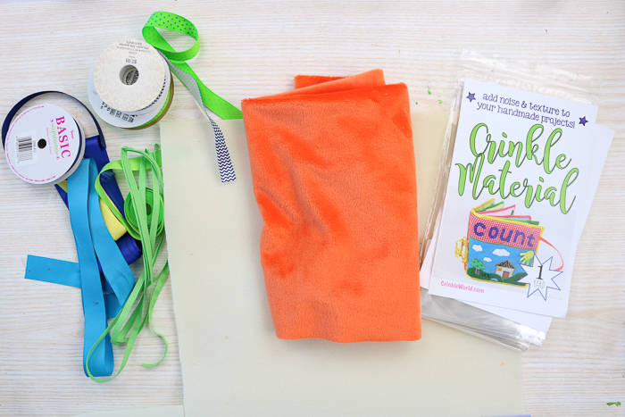 Supplies needed to make a baby tag blanket including crinkle material and minky fabric.