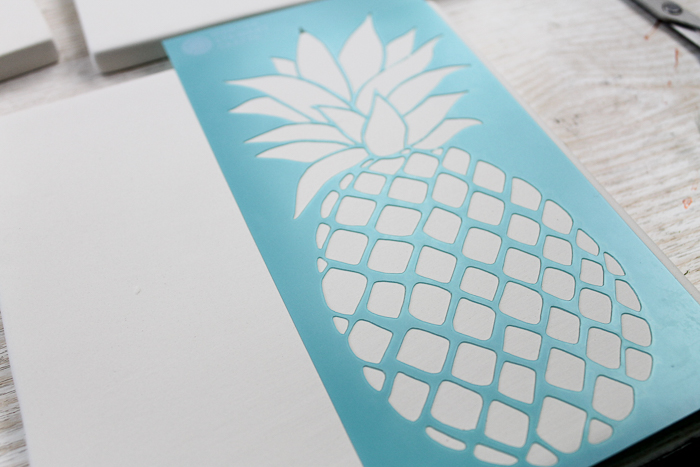 Using a stencil to paint on tile to make ceramic trivets.