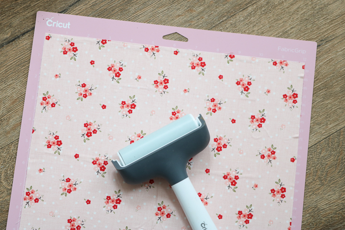 Using brayer to add fabric to fabric mat of Cricut Maker.