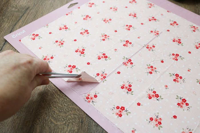 Removing pieces from fabric mat of Cricut Maker with tweezers.
