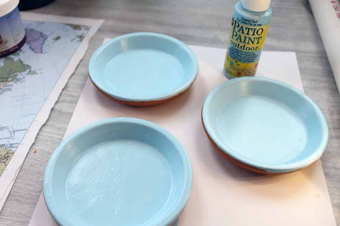Adding outdoor paint to terra cotta saucers to make coasters.