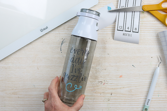 Adding glitter vinyl quote to the front of a water bottle.