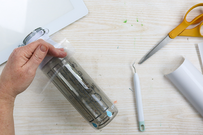 Adding markers for amount of water to drink to a water bottle with glitter vinyl and a Cricut machine.