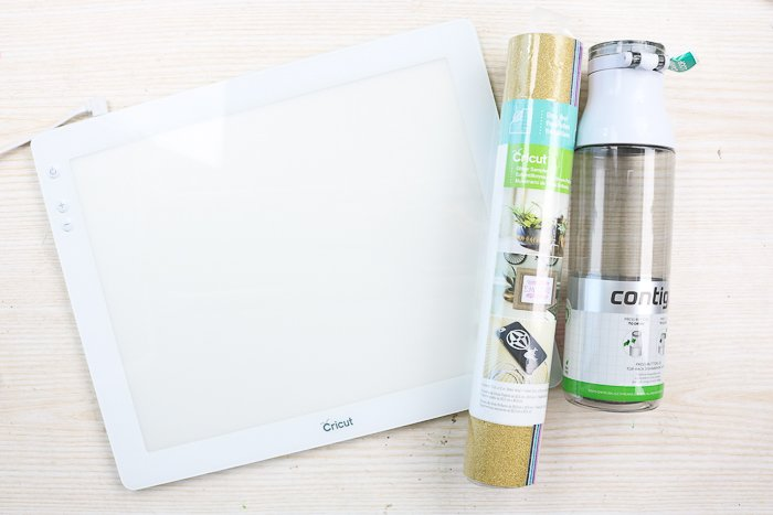 Supplies needed to make a glitter vinyl water bottle using the Cricut BrightPad.