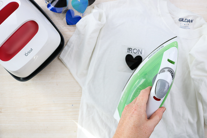 Using an iron to add heat transfer vinyl to a shirt.