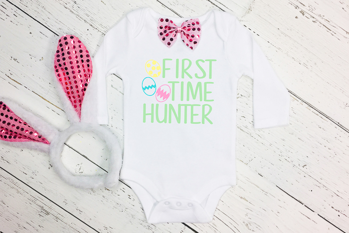 "baby onesie with ""first time hunter"" on it and a pair of rabbit ears"