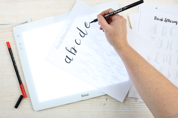 Tracing hand lettering practice sheets over the Cricut BrightPad