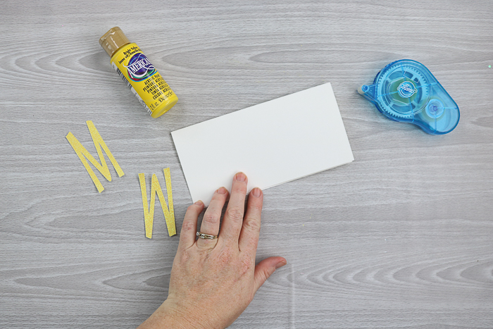 Add cutout letters from the Cricut to the front of a card.