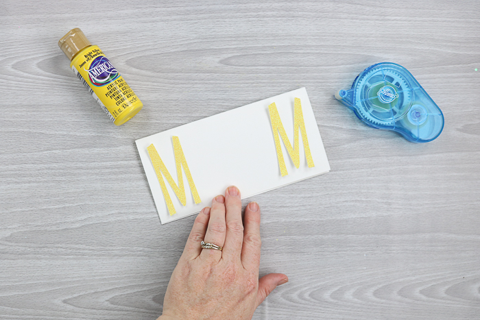 Using adhesive to adhere letters to a Mother's Day card.