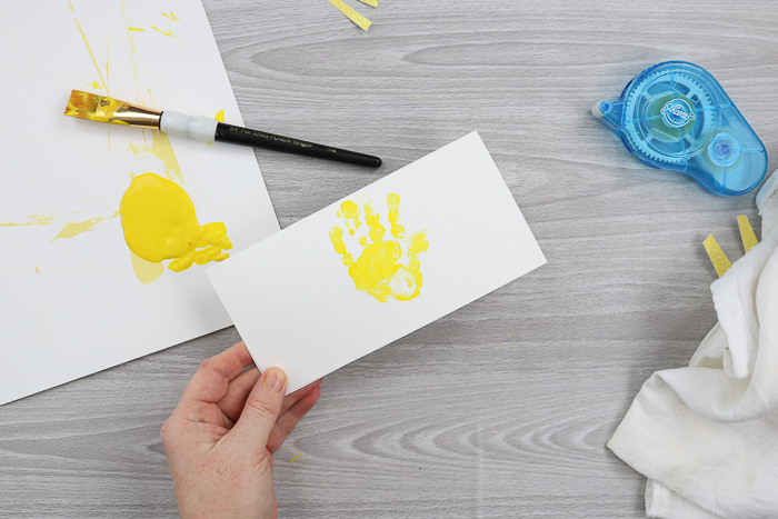 Adding a painted handprint to a Mother's Day card that kids can make.