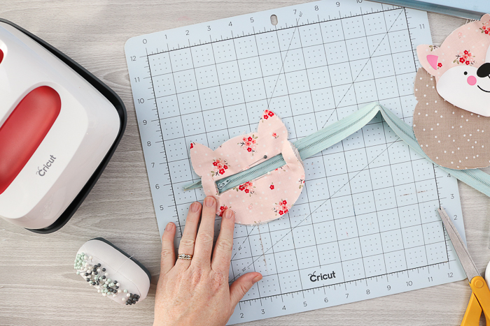 Sewing a zipper into a zipper pouch.