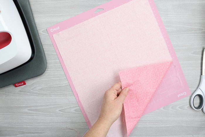 Adding fabric to the pink fabric mat for the Cricut Maker.