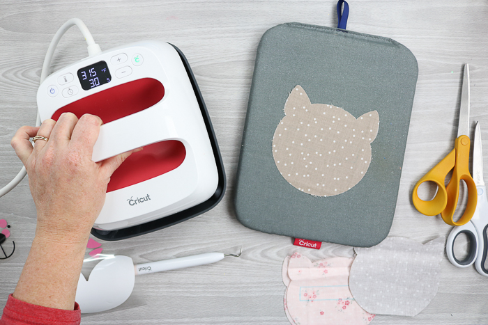 Ironing fabric with the Cricut EasyPress for a zipper pouch tutorial.