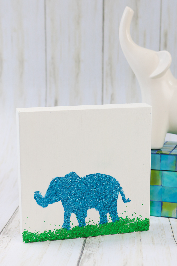 Adding glitter to a piece of elephant art using Mod Podge Ultra