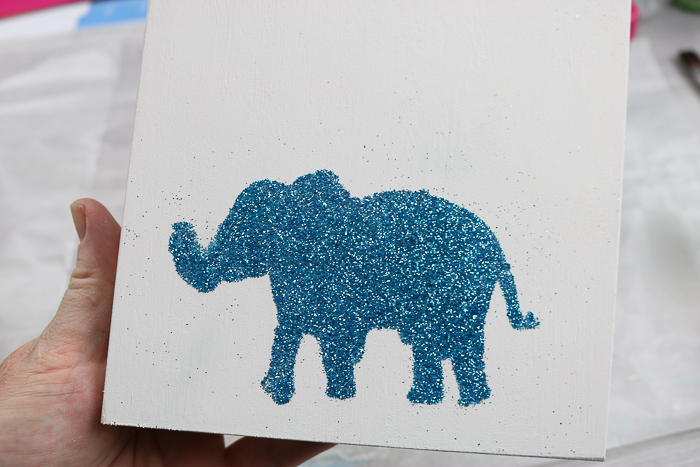 The best glue for glitter on canvas is Mod Podge Ultra