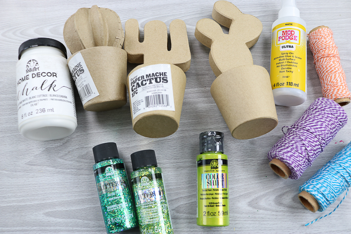 Supplies needed to make a DIY cactus including paper mache cactus and glitterific paint.