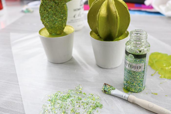 Adding glitterific paint to a paper mache cactus plant