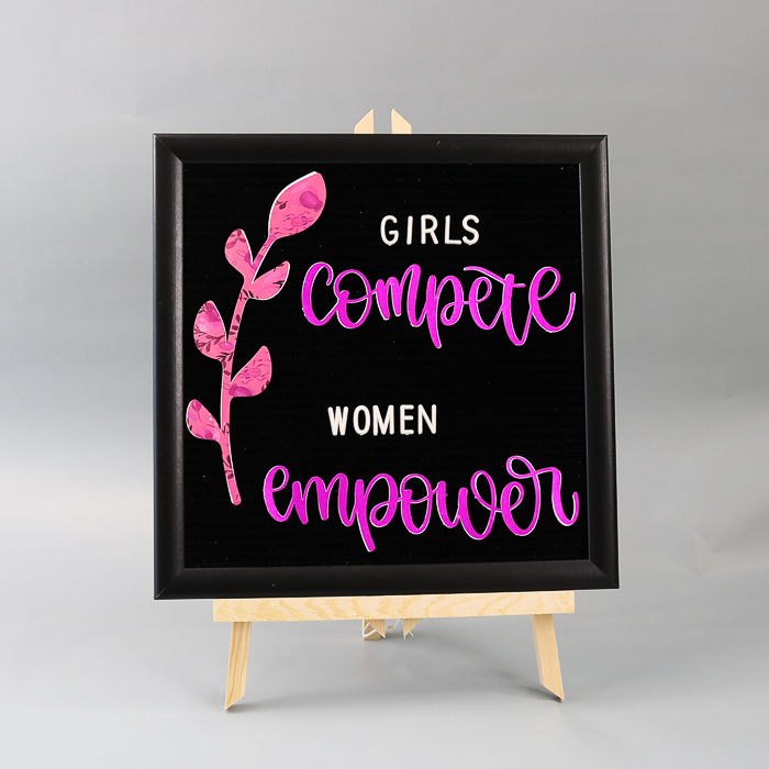 Girls compete women empower quote on a felt letter board