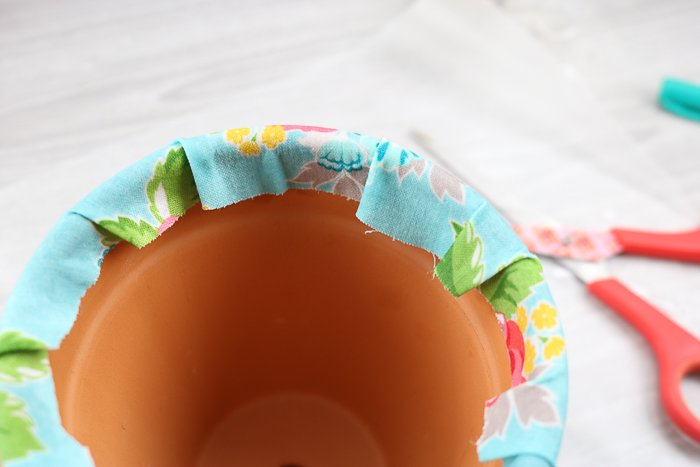 Decorating plant pots with fabric. Wrapping the fabric around the top edge.