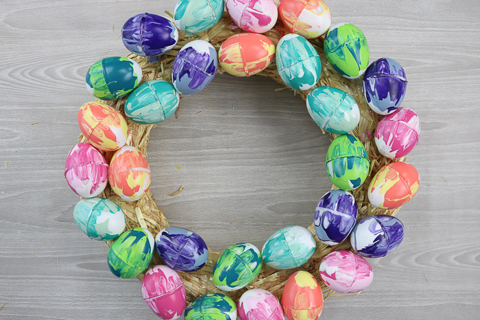 A wreath form covered in marble painted Easter eggs.