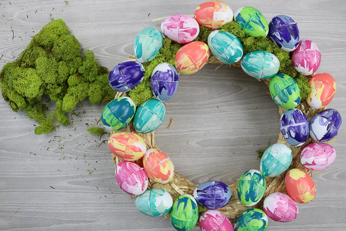 Adding moss to an Easter wreath with marbled eggs.