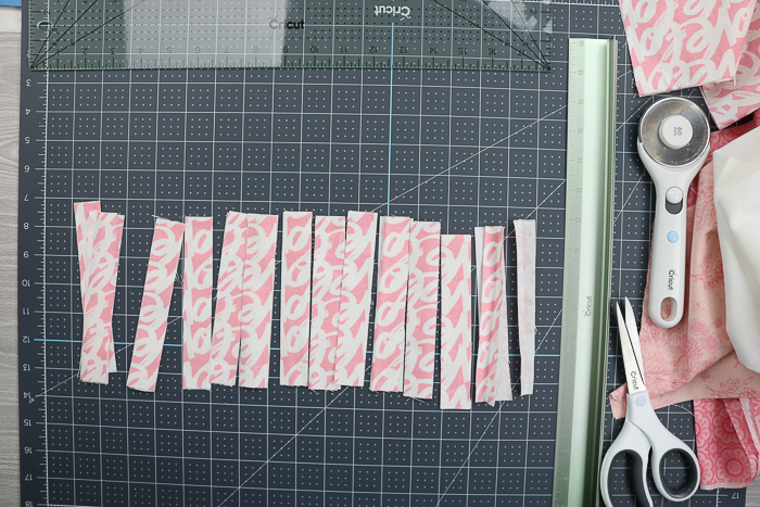 Using the Cricut rotary blade and cutting ruler to cut fabric into strips for a rag wreath.