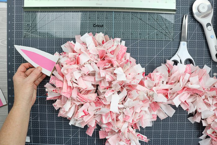 Adding ears to an Easter bunny rag wreath with hot glue