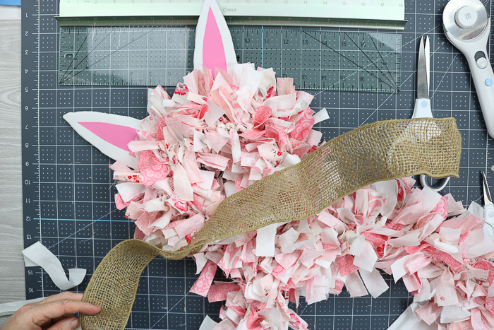 Using burlap ribbon to make a bow for a bunny rag wreath