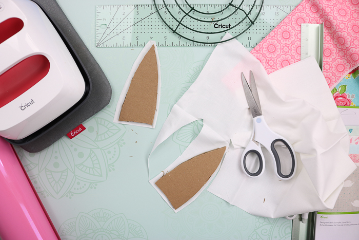 Covering cardboard bunny ears with white fabric to make an Easter rag wreath.