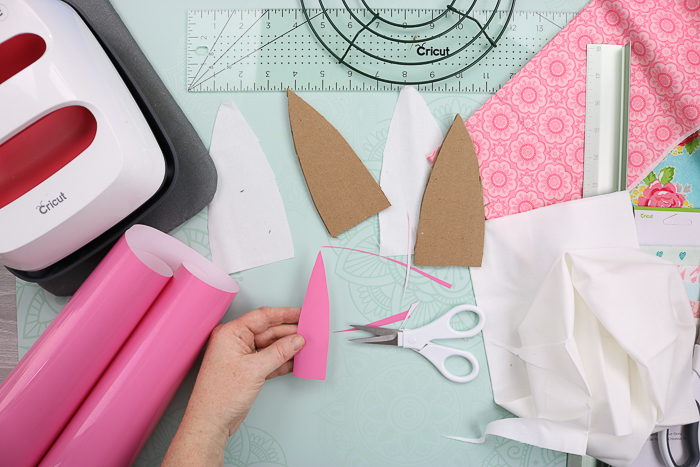 Cutting heat transfer vinyl with scissors to add to the centers of bunny ears.