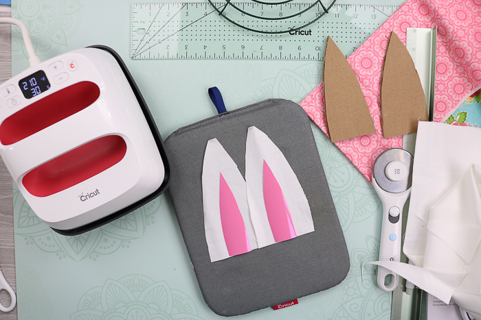 Adding middles to bunny ears using a Cricut EasyPress.