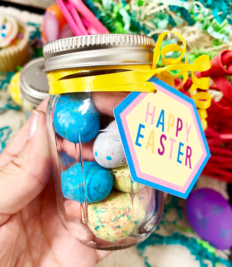 Adding a Happy Easter tag to a mason jar with yellow curling ribbon.