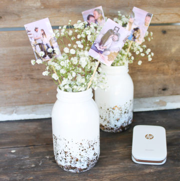 Wedding centerpieces with pictures of bride and groom in a mason jar.