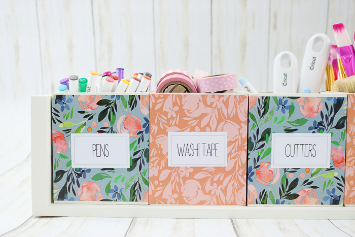 Printable organizing labels on floral wood boxes on a shelf.