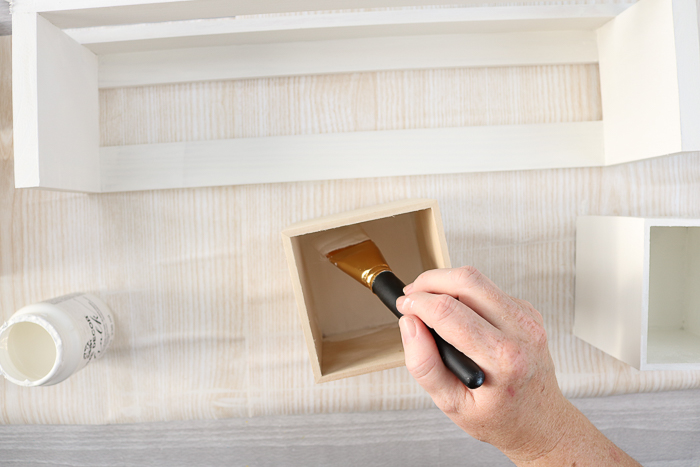 Paint raw wood boxes white to organize craft supplies.