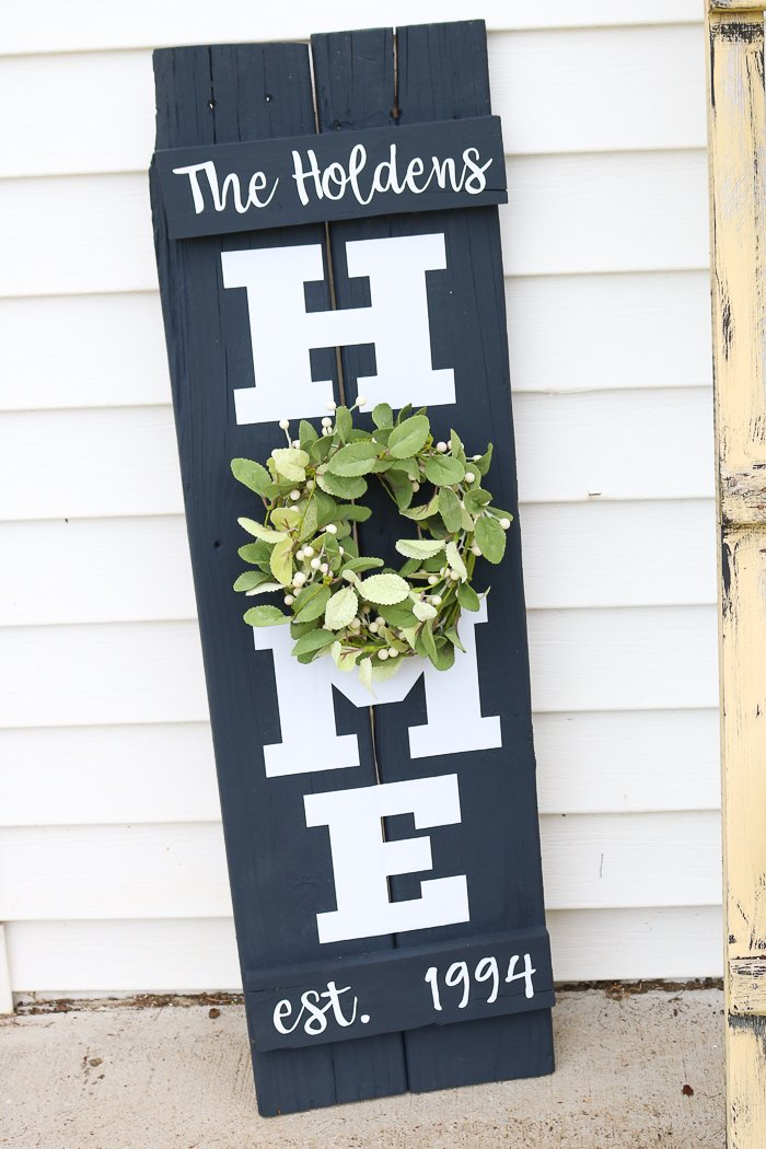 A simple farmhouse style wreath on my DIY home sign is perfect for all seasons