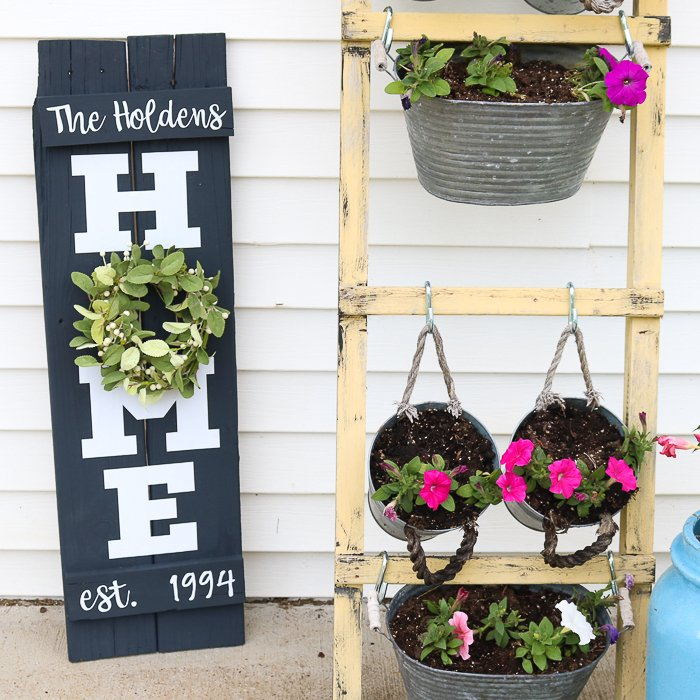 My homemade Home Sign with a Wreath next to a wooden hanging planter stand on my front porch