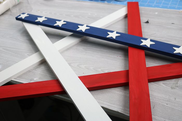 Lay out the painted wood slats into a star shape, then attach with adhesive