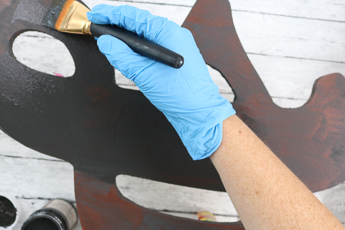 wearing gloves to apply second coat of rust effect paint