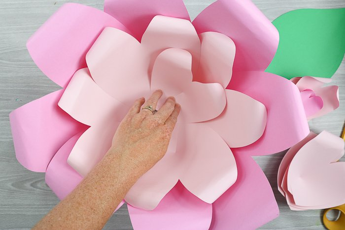 Begin layering the second layer of flower petals, using the smaller paper flower petals