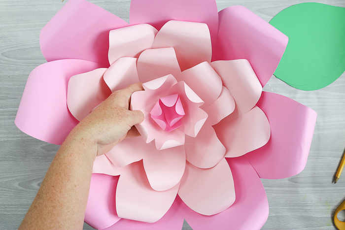 Add the center piece to the large paper flower using hot glue