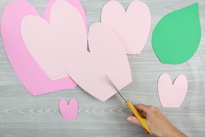 To create the petals for your giant paper flowers, cut paper into the shape of a heart, with the bottom pint cut off.