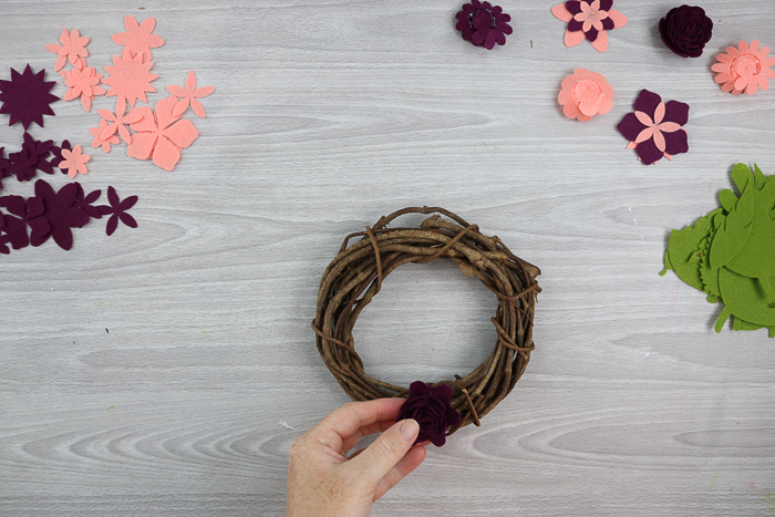 using hot glue to add flowers to a wreath form