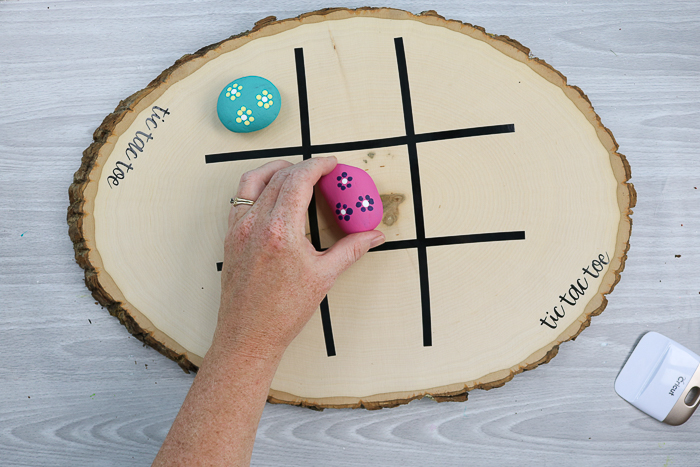 a tic tac toe board game made with rocks