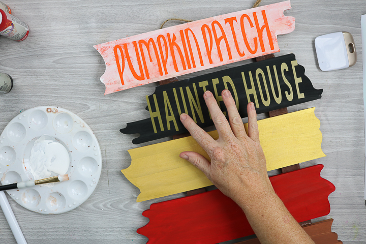 applying cricut vinyl to sign for halloween