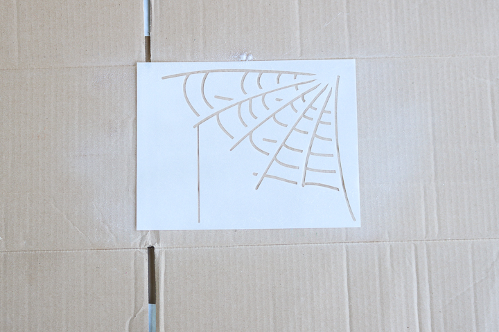 spraying adhesive on back of stencil