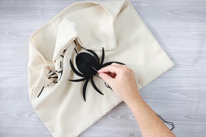 adding felt spider to DIY halloween pillow