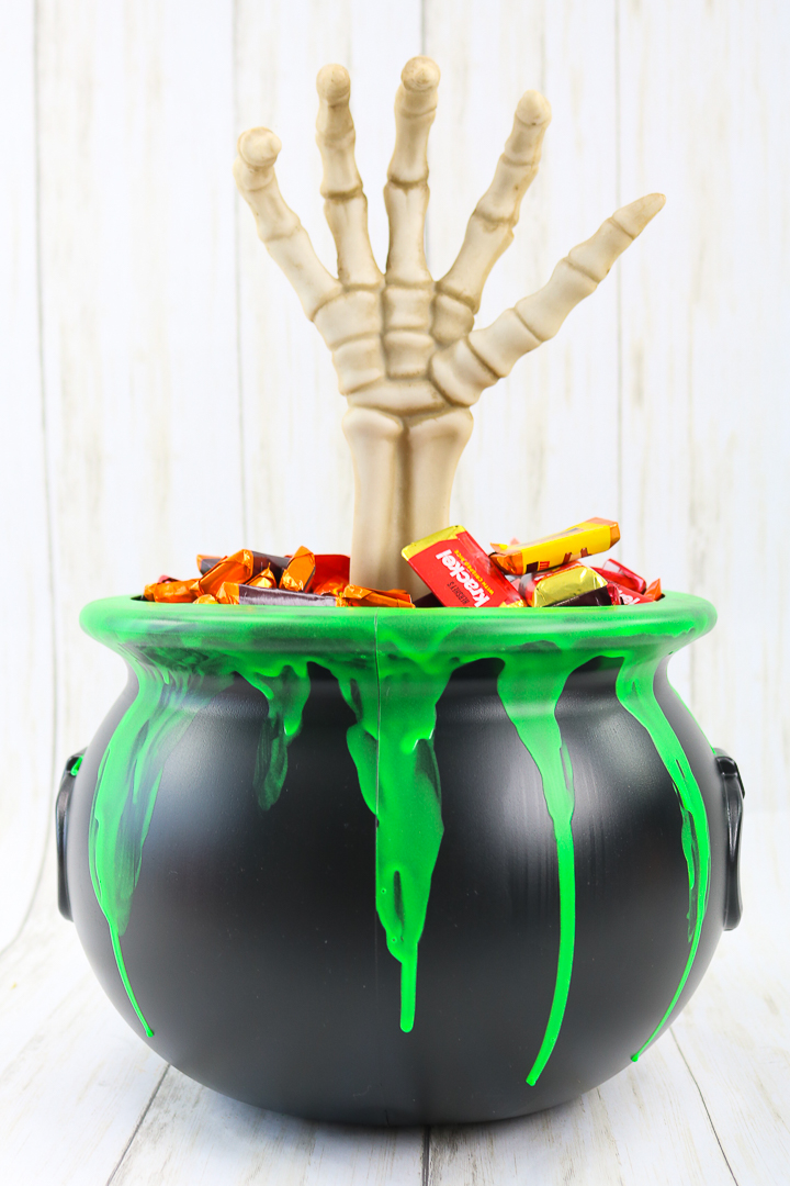 spooky hand in a halloween candy bucket