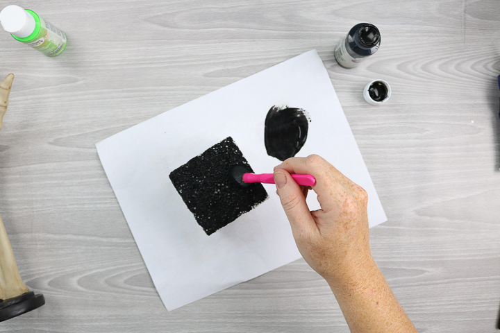 painting a foam block with a sponge brush